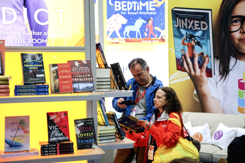 NEW YORK, May 29, 2019 - Visitors look at books at a booth during the 2019 BookExpo America in New York, the United States, May 29, 2019. BookExpo America, one of the largest in North America, runs ...