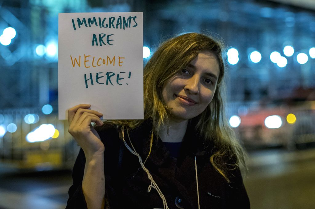 """NEW YORK, Nov. 14, 2016 - A woman holds up a placard reads """"Immigrants are welcome here"""" during a protest against Donald Trump's presidential election victory near the Trump Tower on 5th ..."""