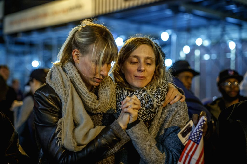 NEW YORK, Nov. 14, 2016 - Two women hold hands as they attend a protest against Donald Trump's presidential election victory near the Trump Tower on 5th Avenue in Manhattan of New York City, the ...