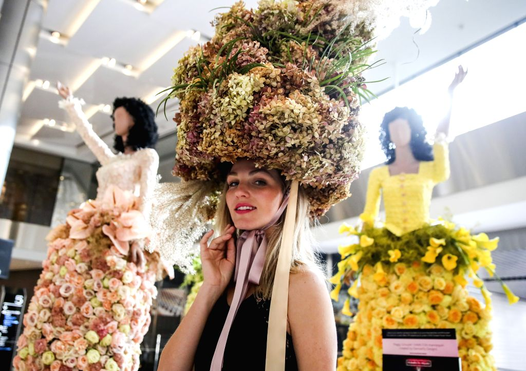NEW YORK, Oct. 25, 2019 - A model with floral headpiece poses for a photo with mannequins with fresh-floral fashion at the Shops and Restaurants at Hudson Yards in New York, the United States, Oct. ...