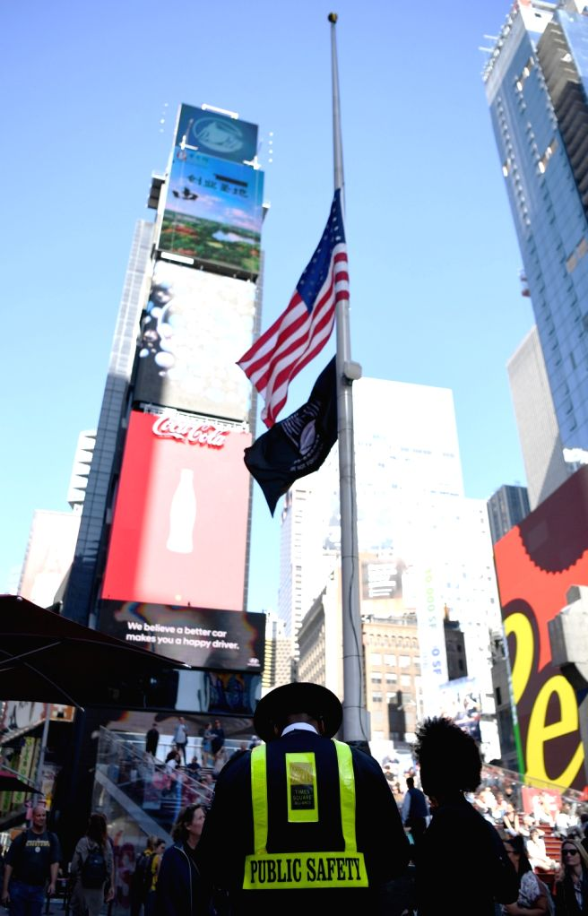 NEW YORK, Oct. 3, 2017 - A Times Square security guard stands in front of a U.S. national flag flying at half mast to mourn the victims of a mass shooting in Las Vegas, at Times Square in New York ...
