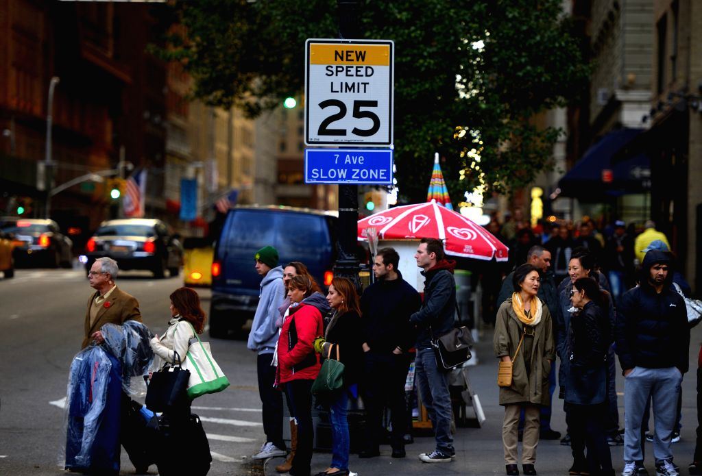 New York: People pass by a traffic sign of new speed limit on the 7th Avenue in Manhattan, New York, the United States, Nov. 7, 2014. A new speed limit of 25 miles an hour, reduced from the original .