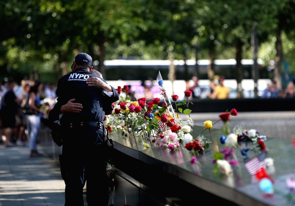 NEW YORK, Sept. 12, 2019 - A policeman comforts a man who comes to mourn the victims of the 9/11 terror attacks at the National September 11 Memorial and Museum in New York, the United States, Sept. ...