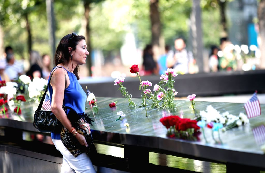 NEW YORK, Sept. 12, 2019 - A woman mourns the victims of the 9/11 terror attacks at the National September 11 Memorial and Museum in New York, the United States, Sept. 11, 2019. People paid their ...