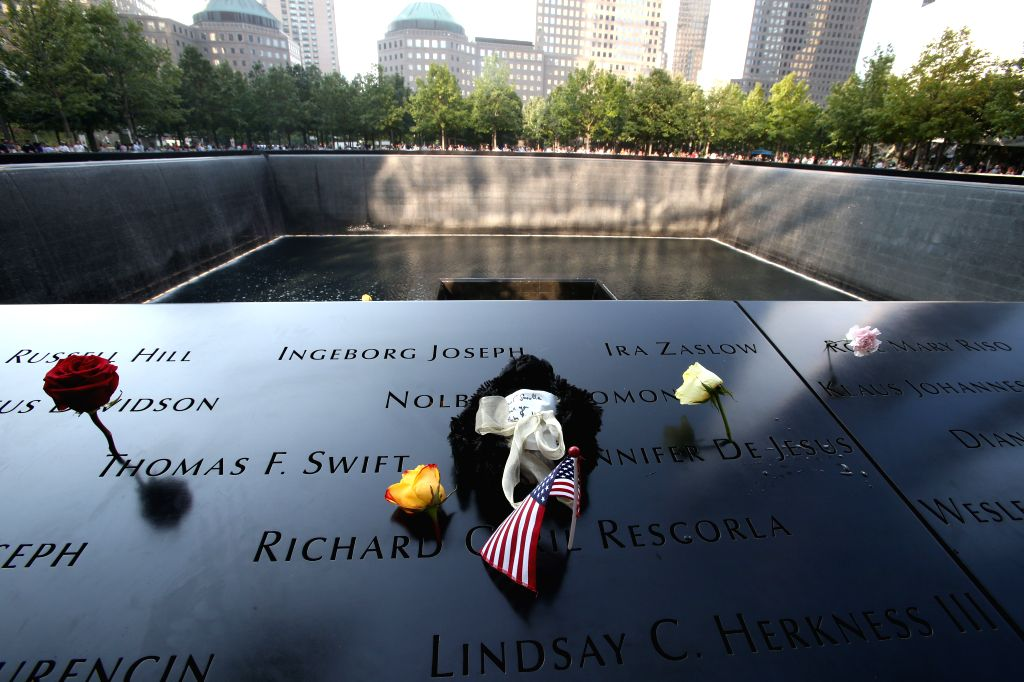 NEW YORK, Sept. 12, 2019 - Flowers and a toy are placed to mourn the victims of the 9/11 terror attacks at the National September 11 Memorial and Museum in New York, the United States, Sept. 11, ...