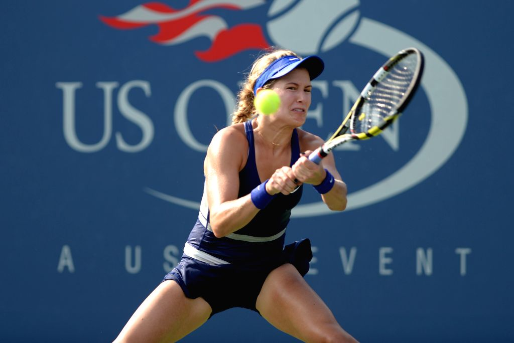 Eugenie Bouchard of Canada returns a shot during the women's singles fourth round match against Ekaterina Makarova of Russia at the 2014 U.S. Open in New York, the