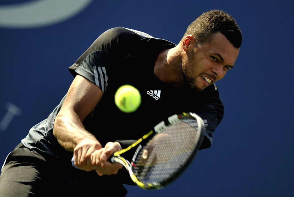 Jo-Wilfried Tsonga of France returs a shot during the men's singles fourth round match against Andy Murray of Britain at the 2014 U.S. Open in New York, the United