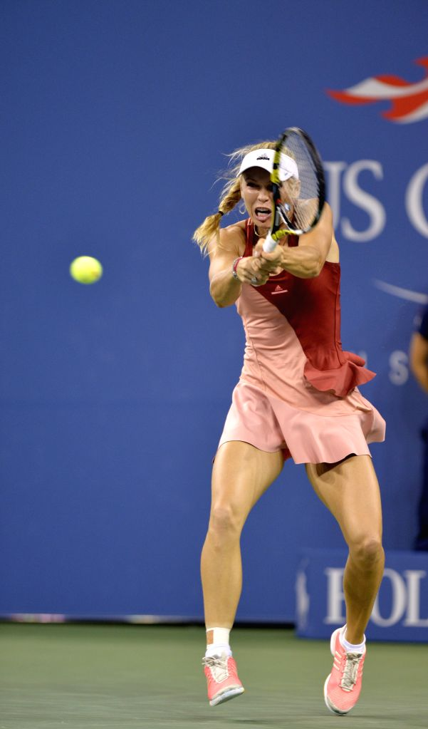 Caroline Wozniacki of Denmark returns a shot against Sara Errani of Italy during the women's singles quarterfinal match at the 2014 U.S. Open in New York, the ...