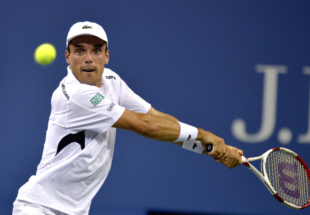 Roberto Bautista Agut of Spain returns the ball during the men's singles fourth round match against Roger Federer of Switzerland at the 2014 U.S. Open in New York,