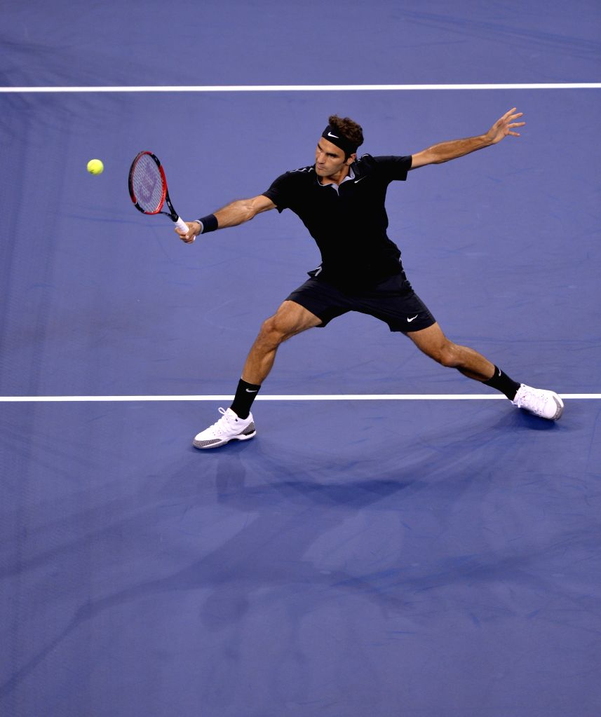 Roger Federer of Switzerland returns a shot to Roberto Bautista Agut of Spain during the men's singles fourth round match at the 2014 U.S. Open in New York, the ...