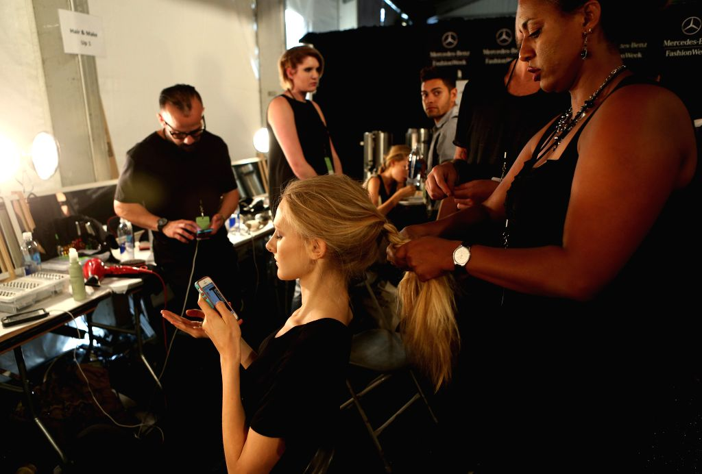 A model has her hair done backstage during the 2015 New York Fashion Week in New York, the United States, on Sept. 4, 2014.