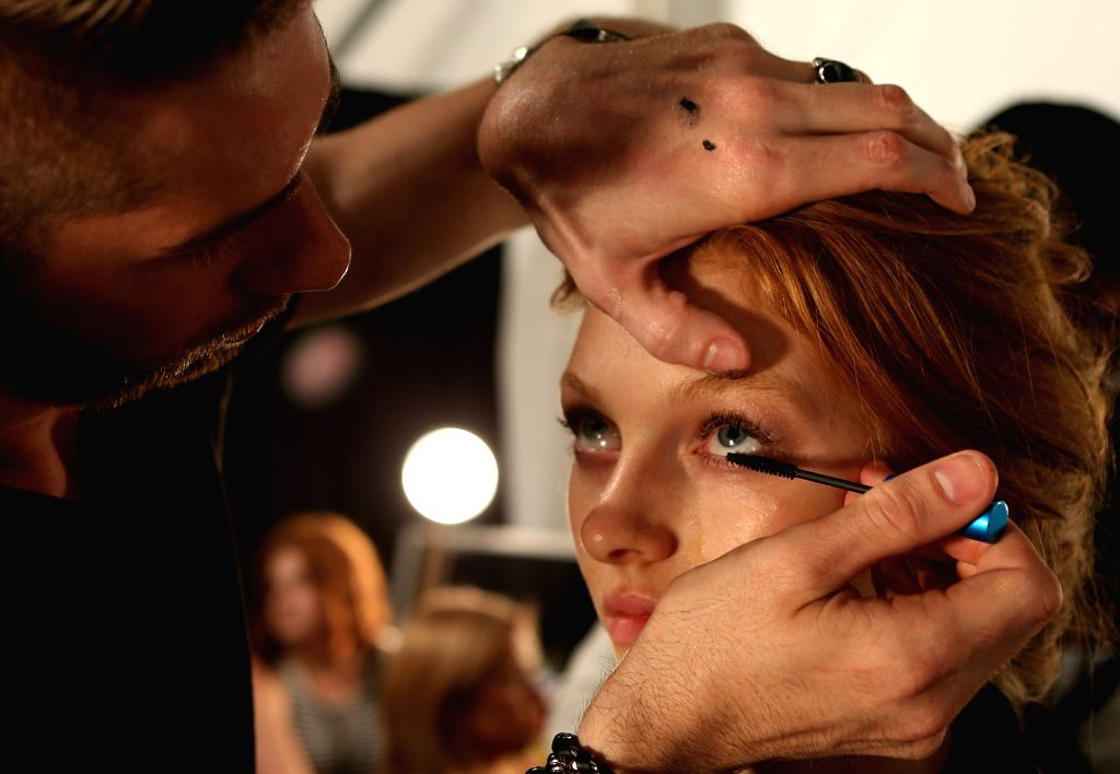 A model has make-up applied backstage during the 2015 New York Fashion Week in New York, the United States, on Sept. 4, 2014.
