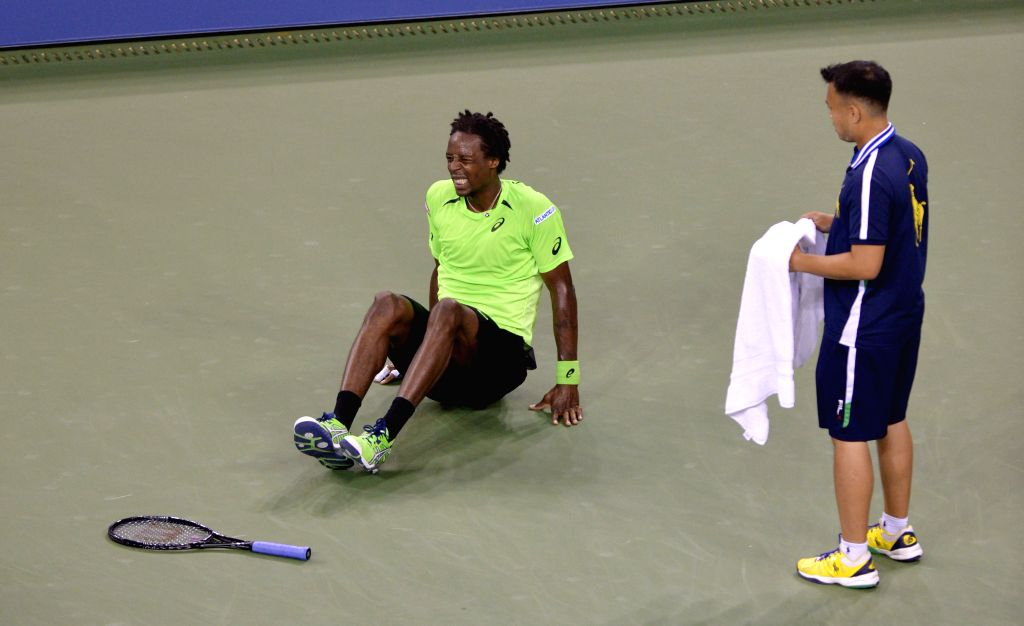 Gael Monfils (L) of France sits on the court after getting injured during the men's singles quarter-final against Roger Federer of Switzerland at the 2014 U.S. ...