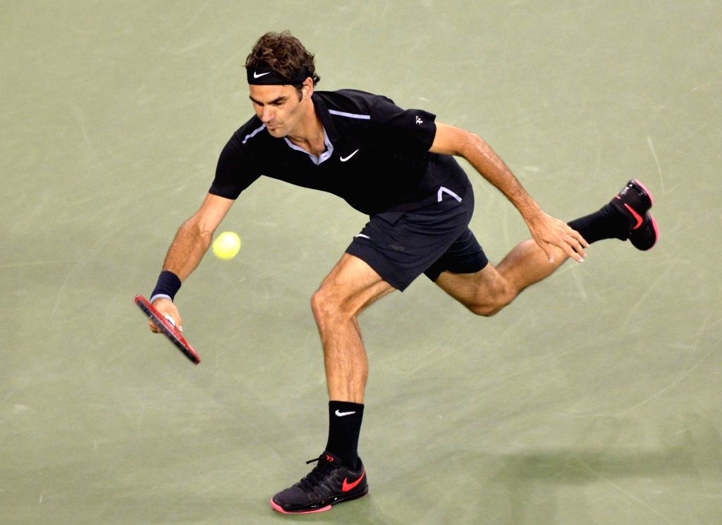Roger Federer of Switzerland returns a hit during the men's singles quarter-final against Gael Monfils of France at the 2014 U.S. Open in New York, the United ...