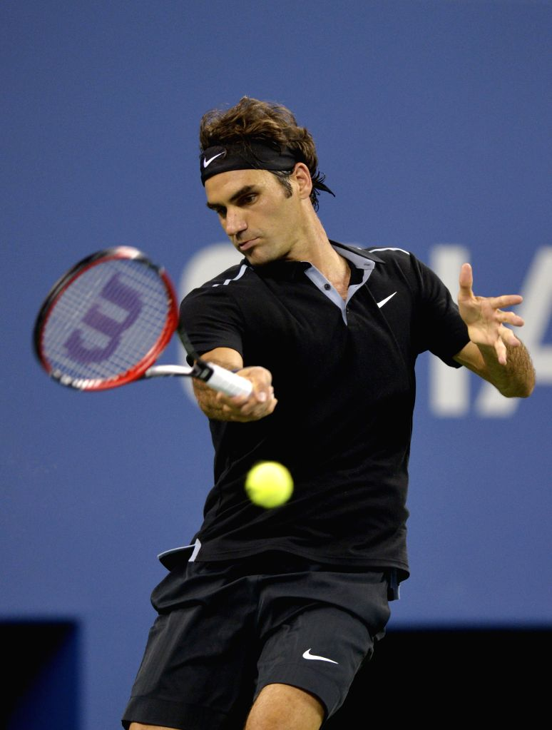 Roger Federer of Switzerland returns a hit during the men's singles quarter-final against Gael Monfils of France at the 2014 U.S. Open in New York, the United ...