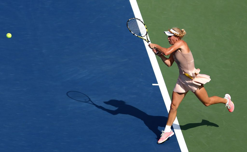 Caroline Wozniacki of Denmark returns a shot to Peng Shuai of China during their women's singles semifinal match at the 2014 U.S. Open in New York, the United ...