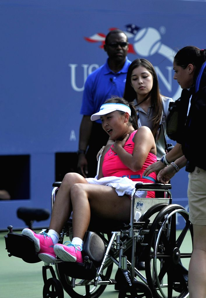Peng Shuai of China (C) grimaces as she is placed in a wheelchair during the women's singles semifinal match against Caroline Wozniacki of Denmark at the 2014 U.S.