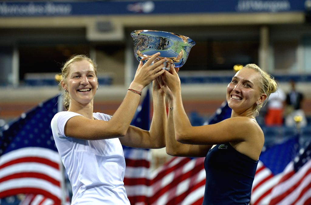 Ekaterina Makarova (L) and Elena Vesnina of Russia pose with the trophy after defeating Martina Hingis of Switzerland and Flavia Pennetta of Italy in their women's - Martina Hingis