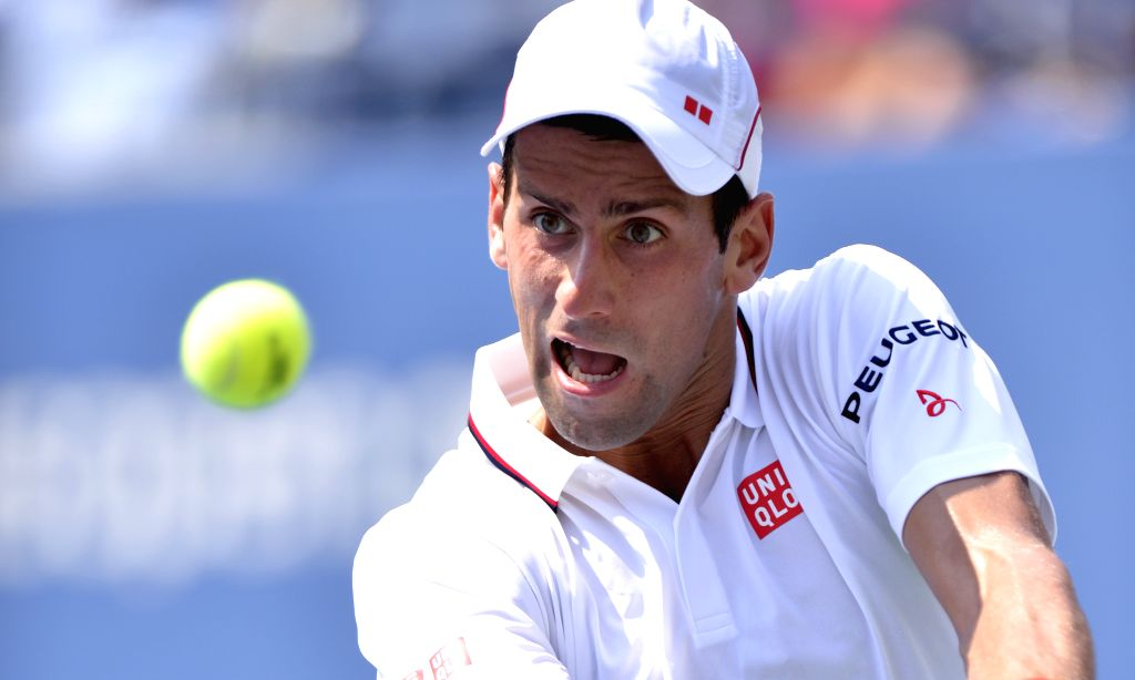 Novak Djokovic of Serbia returns a shot to Kei Nishikori of Japan during their men's singles semifinal match at the 2014 U.S. Open in New York, the United States, .