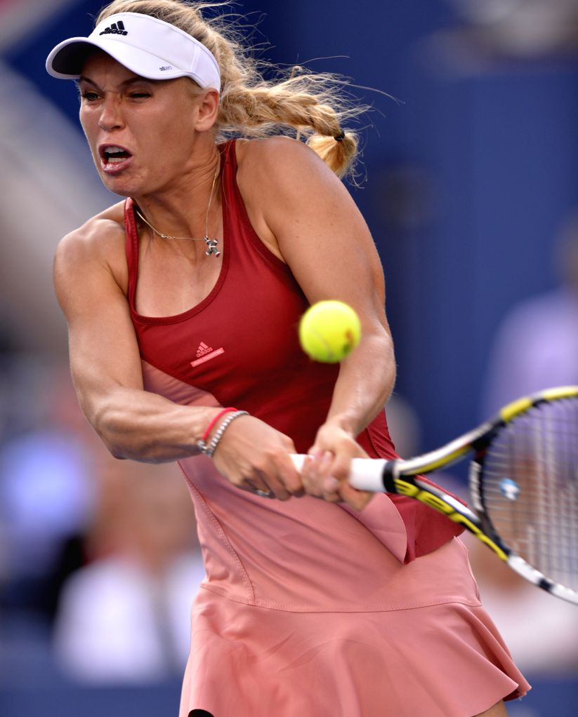 Caroline Wozniacki of Denmark returns a shot against Serena Williams of the United States during their women's singles final match at the 2014 U.S. Open in New ...