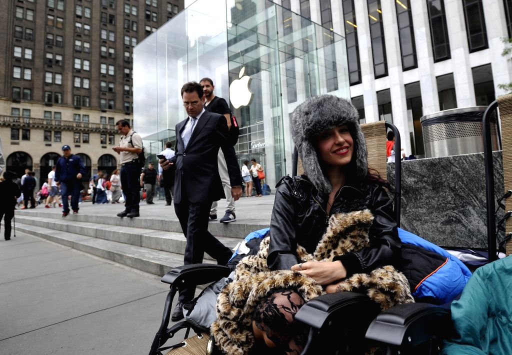 Moon Ray waits to buy Apple's new products outside the Apple Store on 5th Avenue in New York, the United States, on Sept. 9, 2014. Apple Co. introduced two new ...