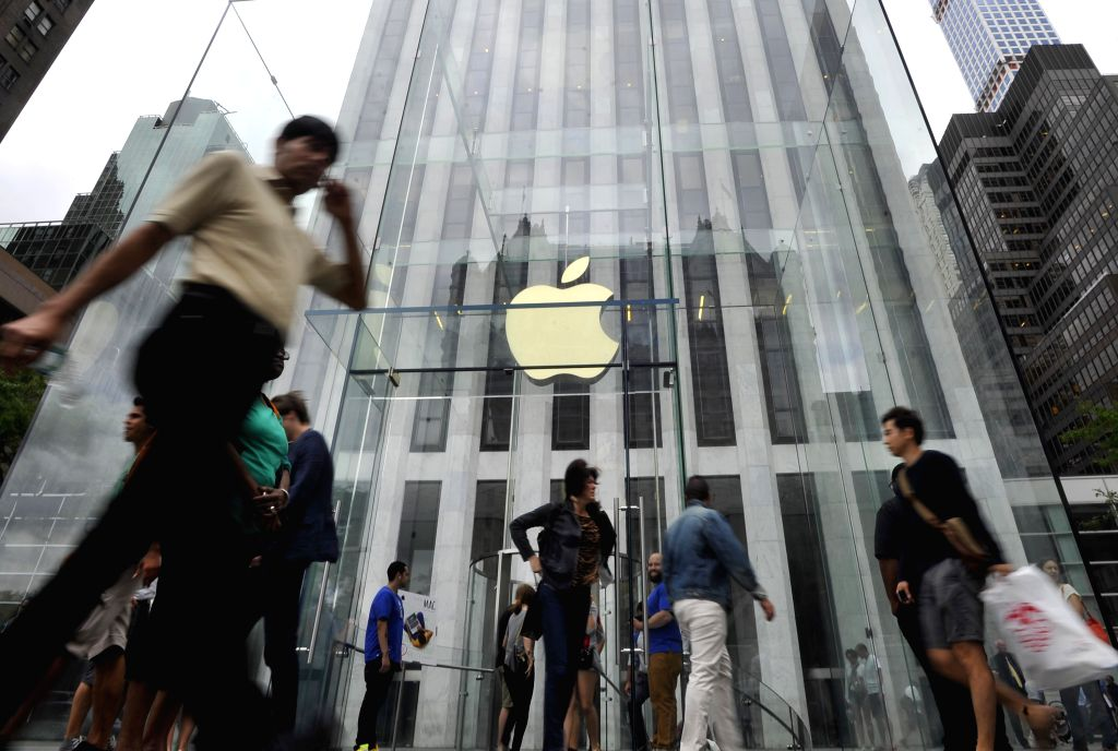 People walk by the Apple Store on 5th Avenue in New York, the United States, on Sept. 9, 2014. Apple Co. introduced two new smart phones, known as iPhone 6 and ...