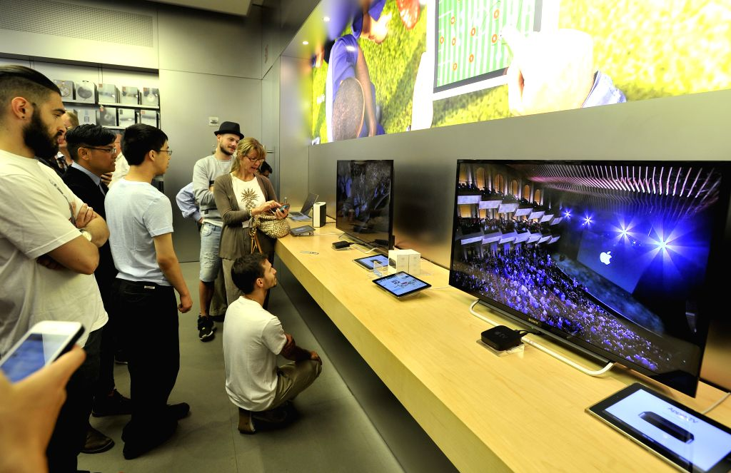 People watch the Apple special event on television in the Apple Store on 5th Avenue in New York, the United States, on Sept. 9, 2014. Apple Co. introduced two new .