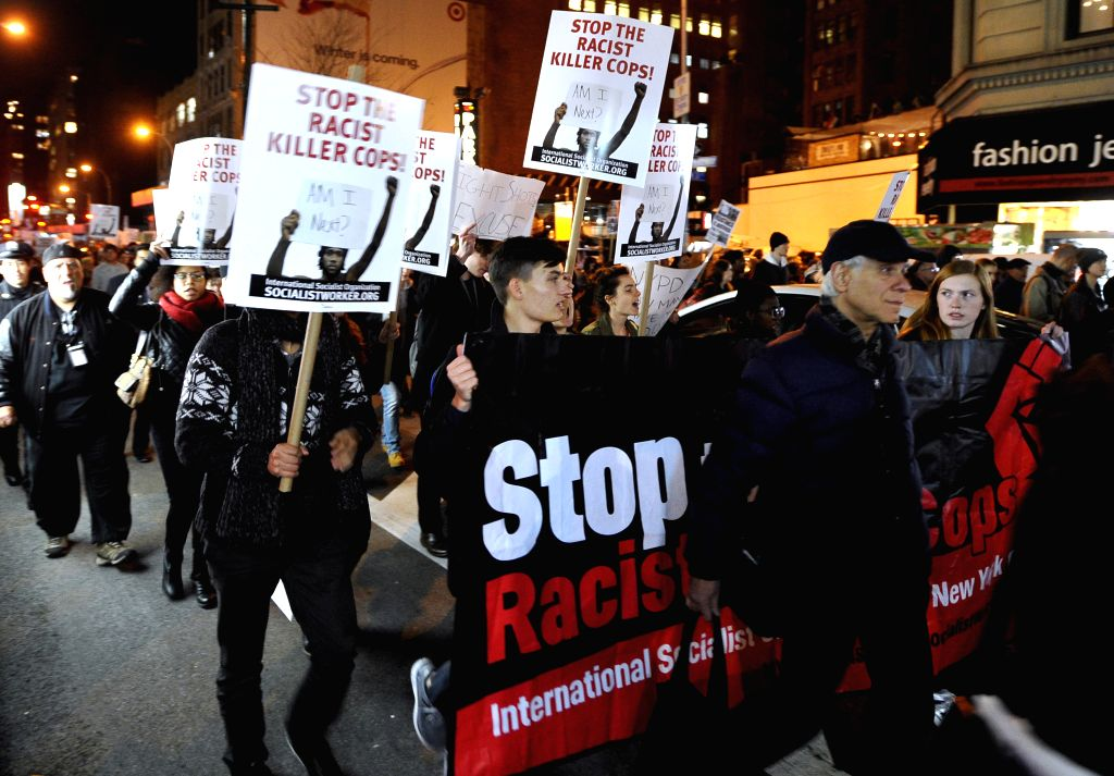New York (U.S.):  People gather for a Ferguson protest in New York Nov. 25, 2014. Tens of thousands of people in 90 cities of the U.S. held rallies on Tuesday to protest against a grand jury's ...