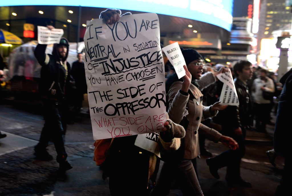 New York (U.S.): Protesters holding banners march at midtown Manhattan in New York, the United States, on Dec. 3, 2014, after a grand jury voted not to indict a white police officer in the chokehold .