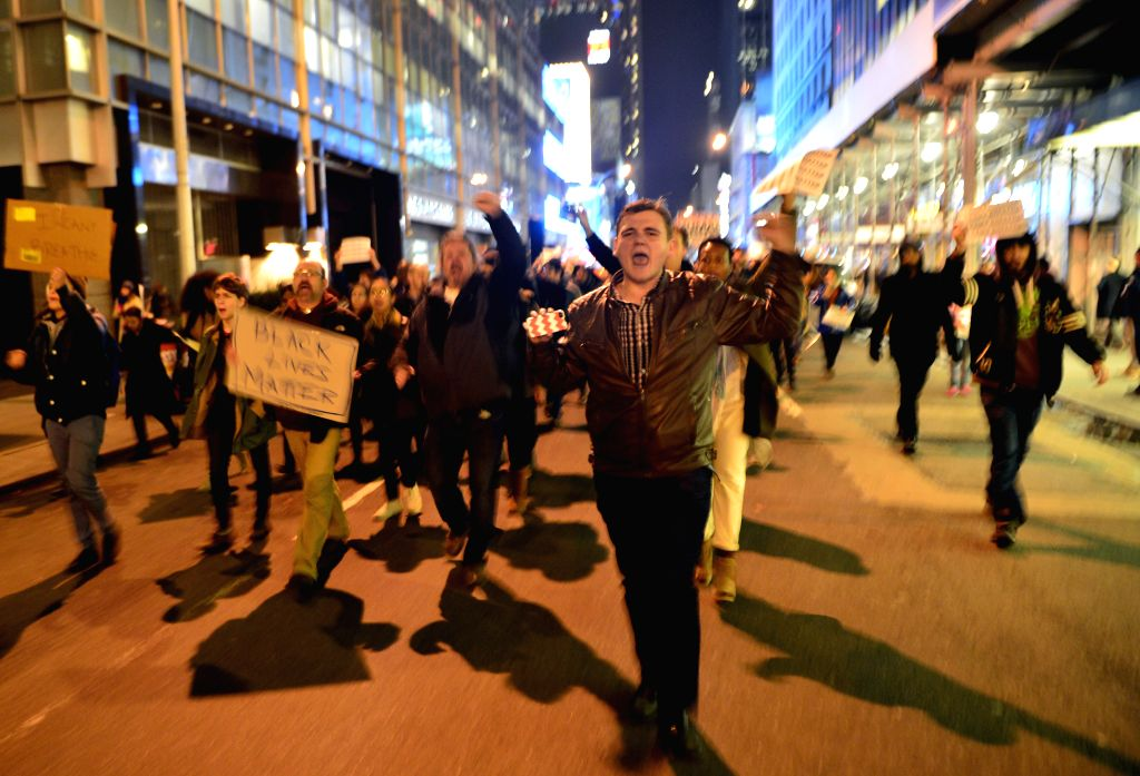 New York (U.S.): Protesters march at midtown Manhattan in New York, the United States, on Dec. 3, 2014, after a grand jury voted not to indict a white police officer in the chokehold death of a black