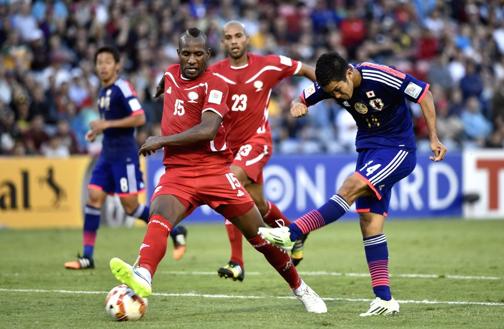 Yoshinori Muto (R) of Japan shoots the ball during a Group D match against Palestine at the AFC Asian Cup in Newcastle, Australia, Jan. 12, 2015. Japan won 4-0. ..
