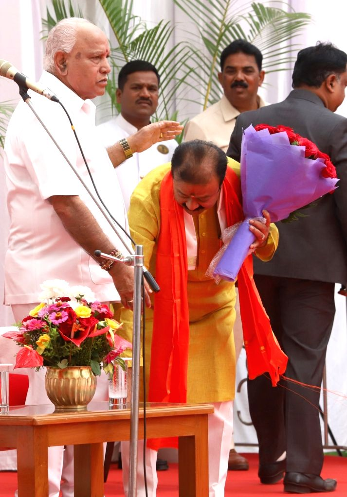 Newly inducted Karnataka Cabinet Minister KC Narayana Gowda seeks the blessings of Chief Minister B.S. Yediyurappa after taking oath, at a swearing-in ceremony held at Raj Bhavan, in ... - K
