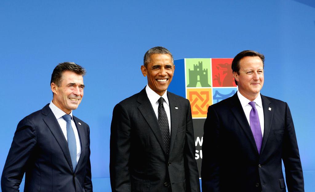 The NATO Secretary General Anders Fogh Rasmussen (L), U.S. President Barack Obama (C) and British Prime Minister David Cameron pose at the NATO Summit 2014 in ... - David Cameron
