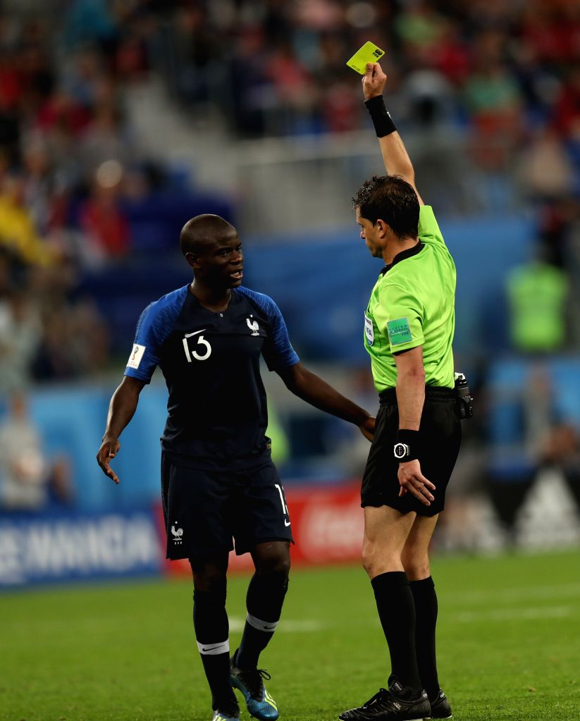 Ngolo Kante (L) of France receives a yellow card from referee Andres Cunha during the 2018 FIFA World Cup semi-final match between France and Belgium in ...