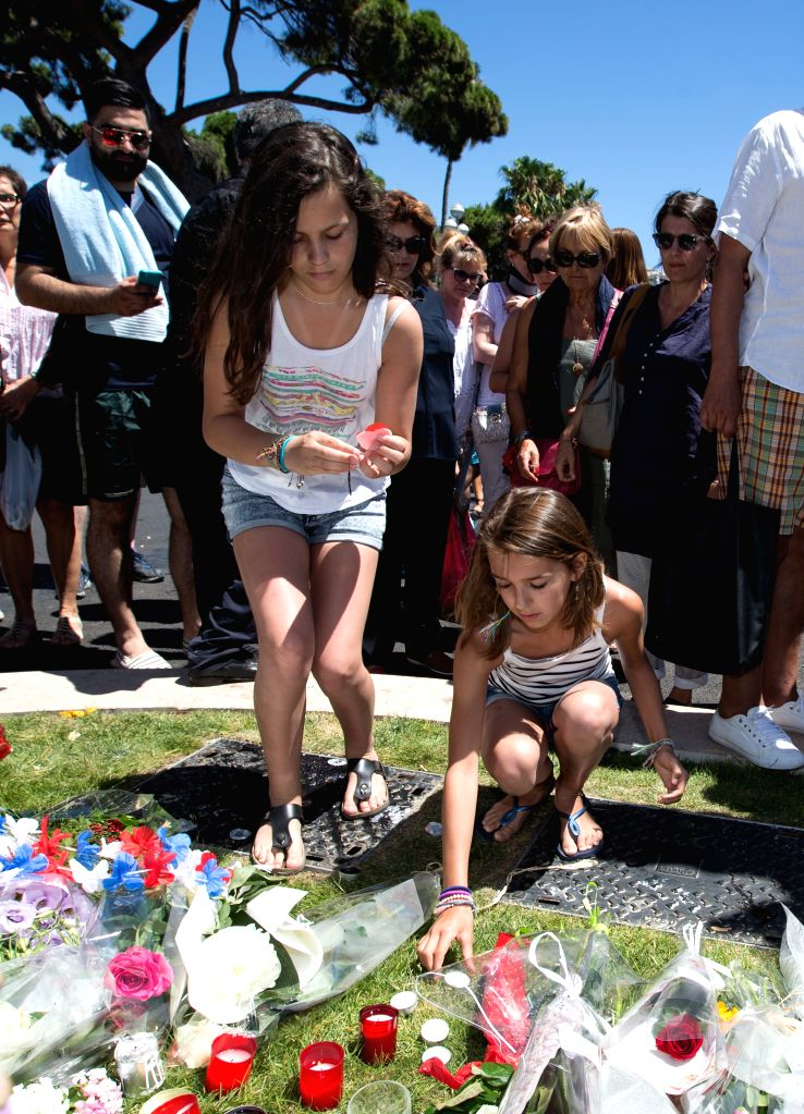 NICE, July 15, 2016 - People offer flowers and candles to the victims near the site of the terrorist attack in Nice, France, July 15, 2016. The death toll rises to 84 from an attack in which a truck ...