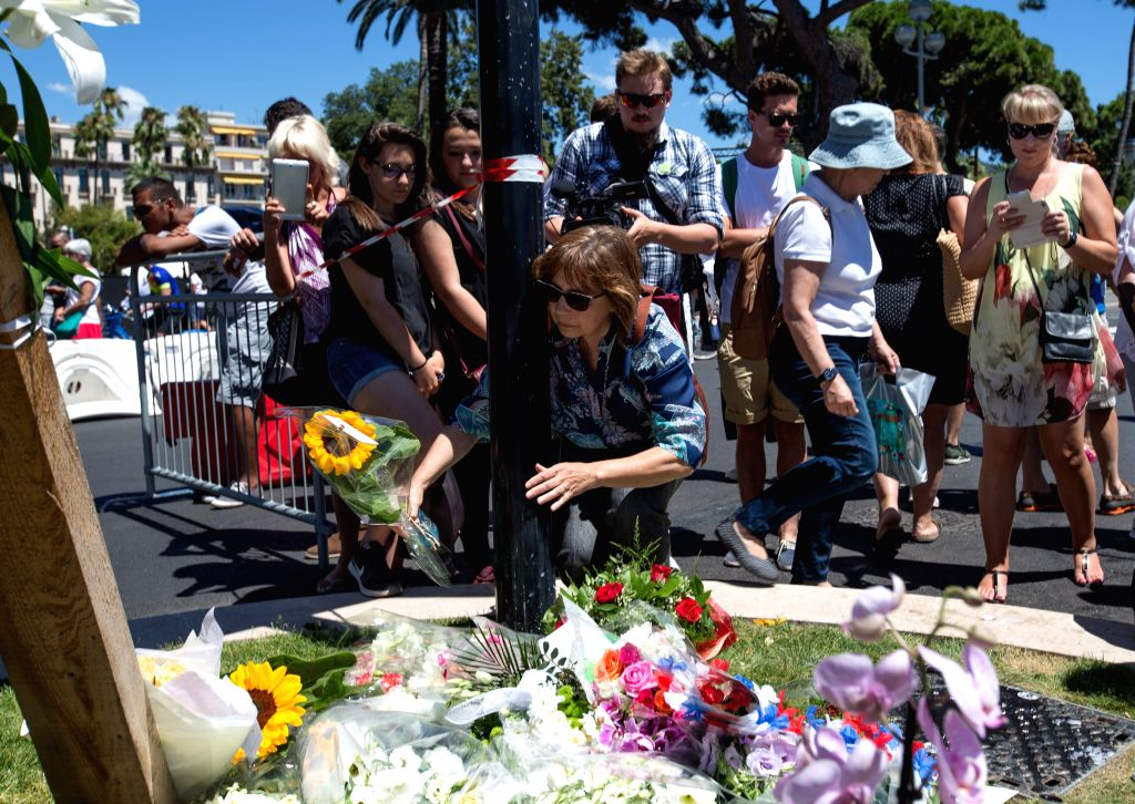 NICE, July 15, 2016 - People offer flowers to the victims near the site of the terrorist attack in Nice, France, July 15, 2016. The death toll rises to 84 from an attack in which a truck rammed into ...