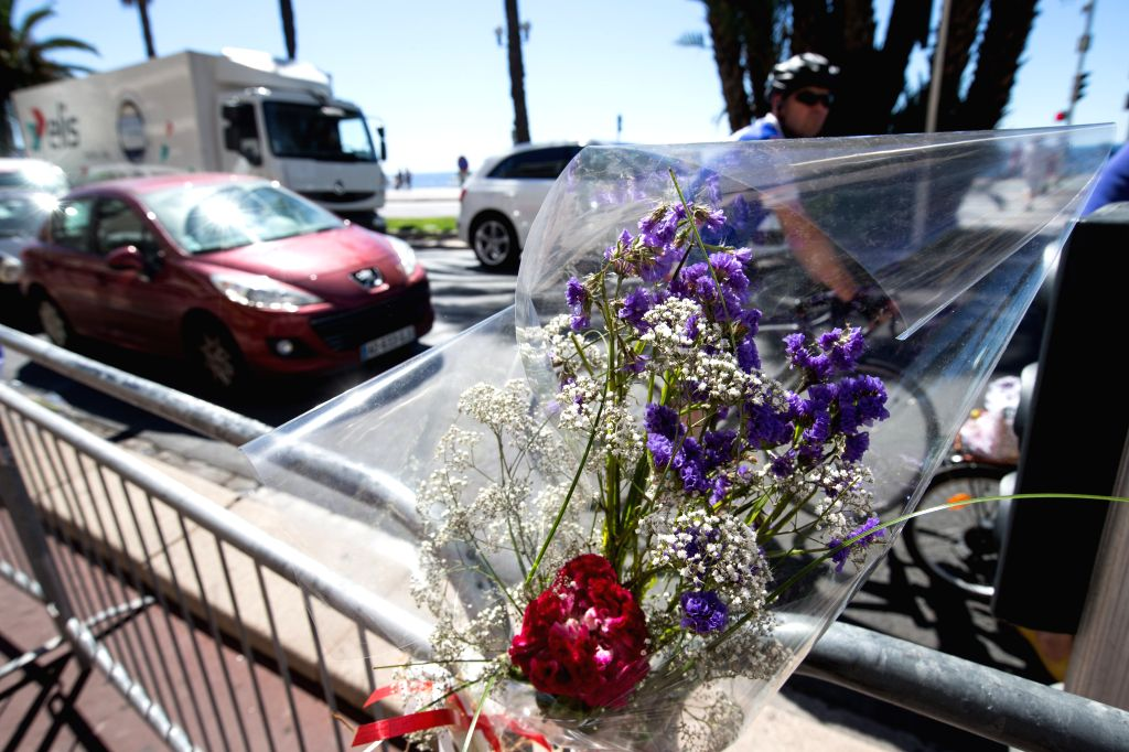 NICE, July 16, 2016 - A man rides past flowers offered to the victims of the terrorist attack of Promenade des Anglais in Nice, France, July 16, 2016. The Islamic State (IS)-linked news agency Amaq ...