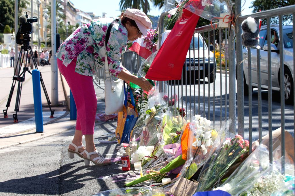 NICE, July 16, 2016 - A woman waters flowers offered to the victims of the terrorist attack of Promenade des Anglais in Nice, France, July 16, 2016. The Islamic State (IS)-linked news agency Amaq ...