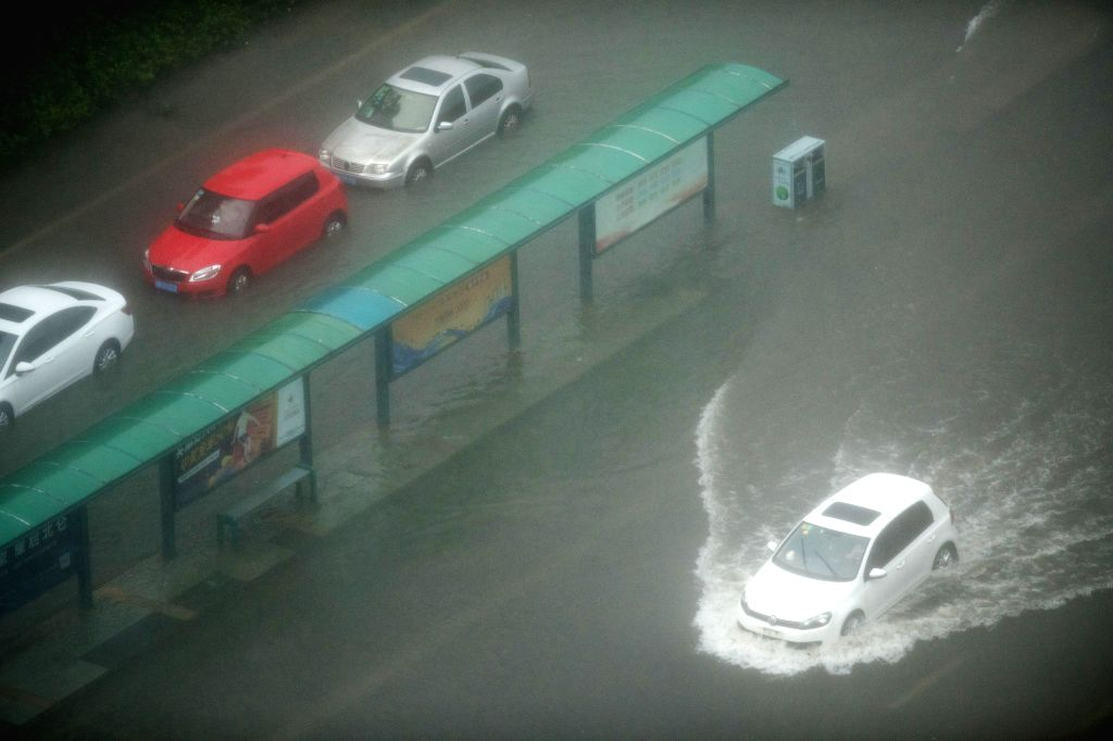 NINGBO, Aug. 10, 2019 (Xinhua) -- Cars run on a waterlogged street in Beilun District of Ningbo, east China's Zhejiang Province, Aug. 10, 2019. China's National Meteorological Center issued an orange alert for Typhoon Lekima on Saturday morning, as i