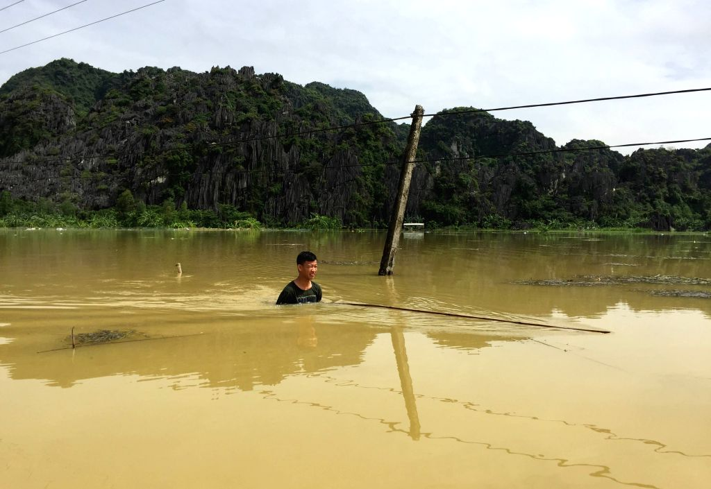 NINH BINH (VIETNAM), Oct. 12, 2017 A man wades through flood water in Ninh Binh province, northern Vietnam, on Oct. 12, 2017. Landslides and floods triggered by heavy rain over the past ...