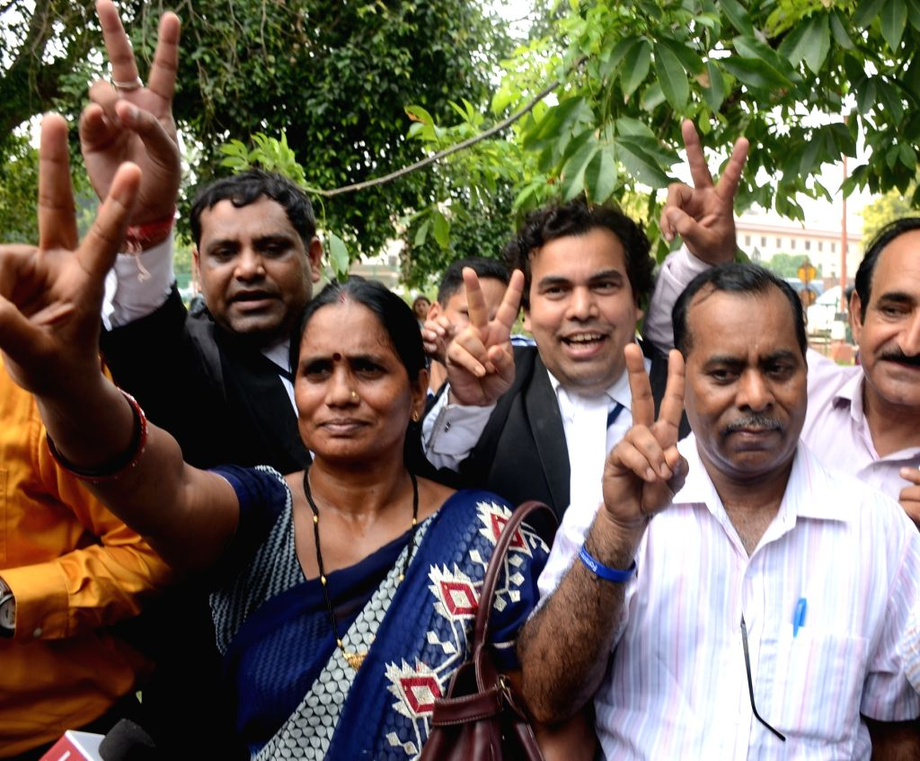 Nirbhaya's parents Asha Devi and Badri Singh show victory sign after the Supreme Court reaffirmed its verdict upholding the death sentence to four convicts who gangraped and murdered ... - Badri Singh
