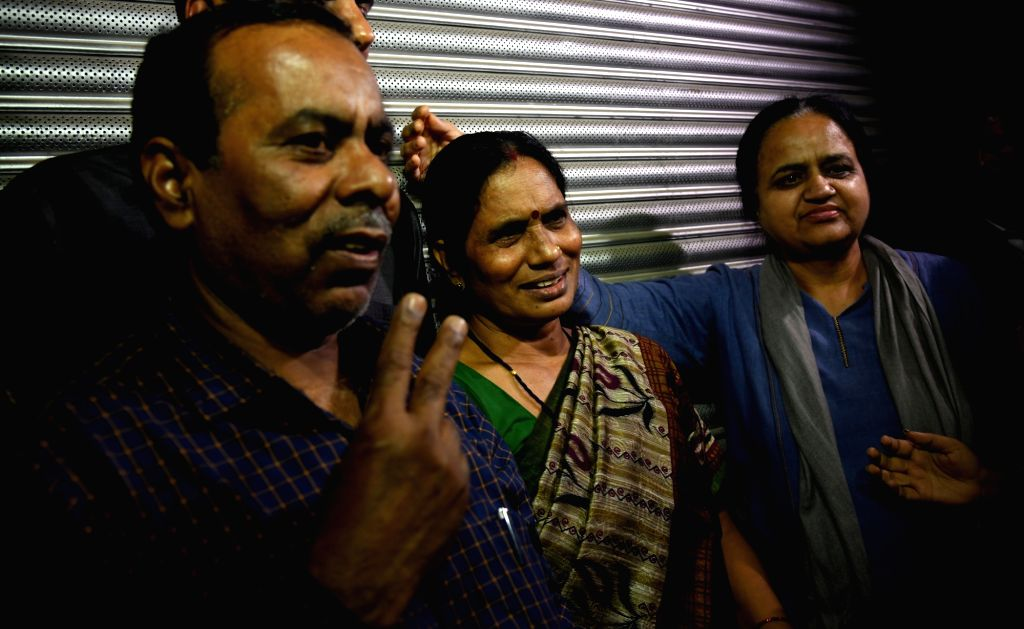 Nirbhaya's parents Asha Devi and Badrinath Singh show victory sign after the hanging of four convicts in the 2012 Nirbhaya rape case, in New Delhi on March 20, 2020. - Badrinath Singh
