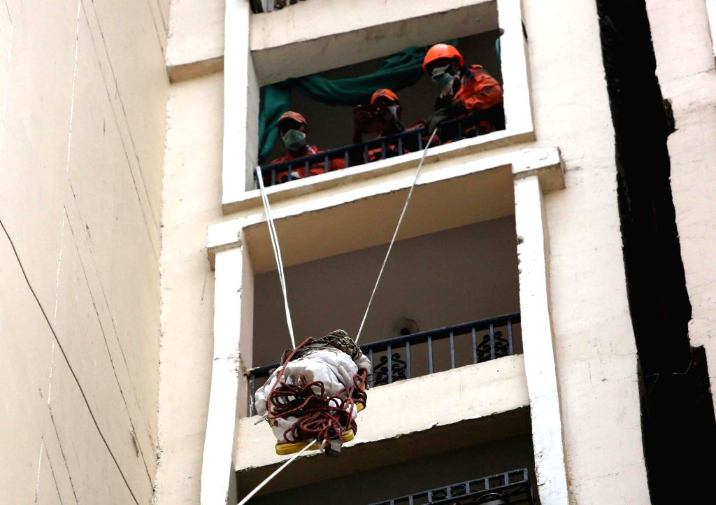 Noida: NDRF personnel retrieve the body of a woman that was lying between two high-rise buildings near Amrapali Silicon City Society in Noida, on July 2, 2019. The discovery was made after residents complained about foul smell. (Photo: IANS)