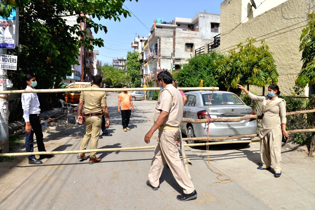 Noida: Police personnel seal the entry to Chauda Village, one of the 22 areas in Noida identified by the district administration as 'hotspots' defined as any location that has seen atleast one person test positive for COVID-19, sealed during the 21-d