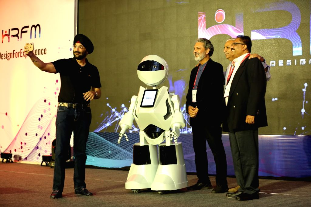 Noida: Tech Mahindra Chief People Officer Harshvendra Soin clicks selfies with the first Human Resource (HR) Humanoid K2 introduced by Tech Mahindra Ltd for its Noida Special Economic Zone Campus, on June 24, 2019. (Photo: IANS)