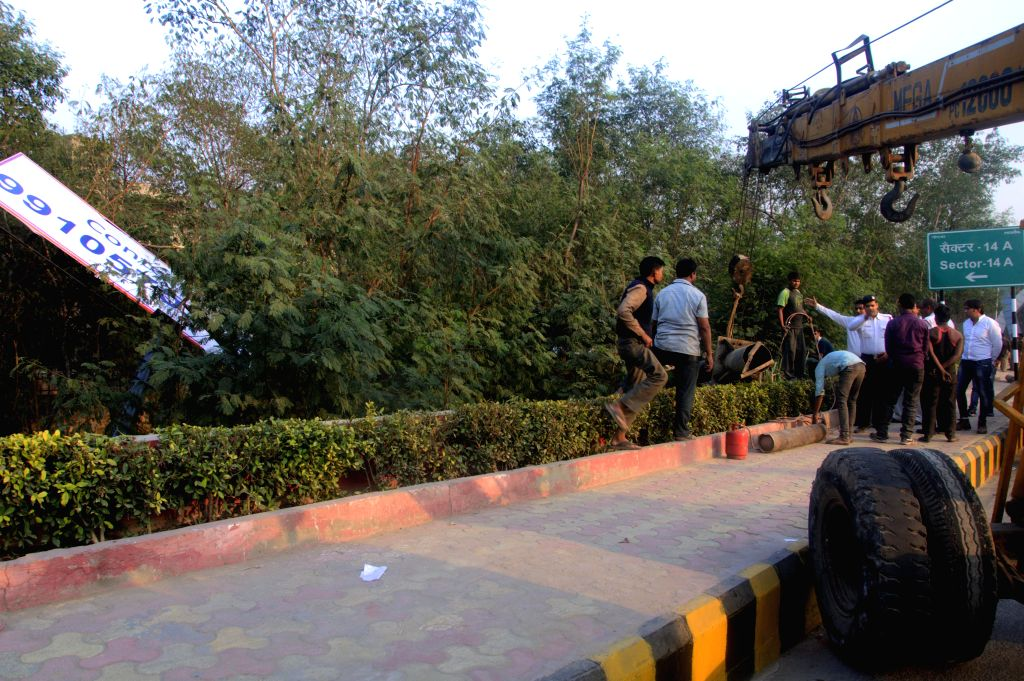 The Noida authorities pull down illegal hoardings from no man's land between Delhi and Noida in order to enhance the view of nearby Buddha statue.
