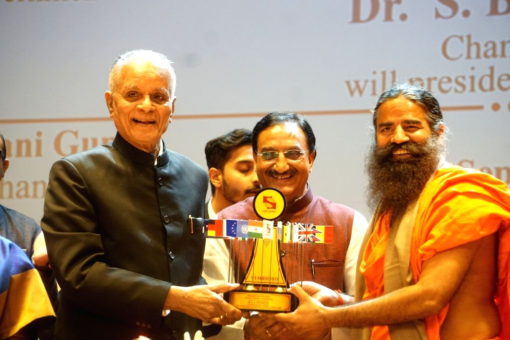 Noida: Yoga Guru Baba Ramdev being felicitated by Symbiosis International University Chancellor S. B. Mujumdar during the inauguration of the University's Noida campus, on Sep 24, 2019. Also seen Union Human Resource Development Minister Ramesh Pokhr - Ramesh Pokhriyal
