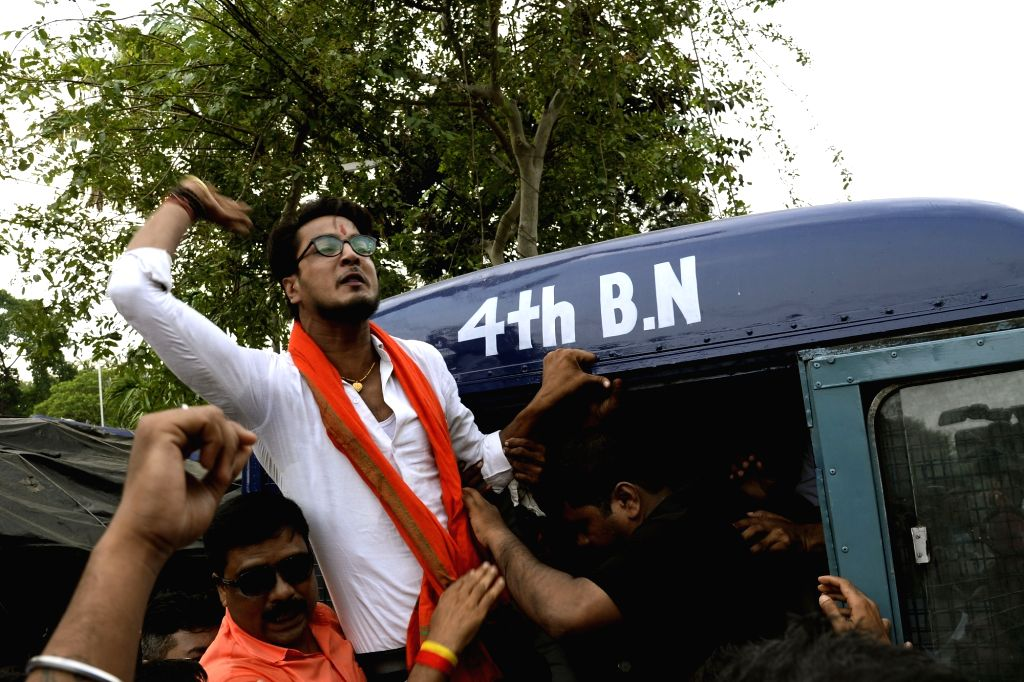 North 24 Parganas: Police take away BJP worker agitating against the alleged killing of  party workers during a clash between the saffron outfit and the ruling Trinamool Congress at Sandeshkhali, in ...
