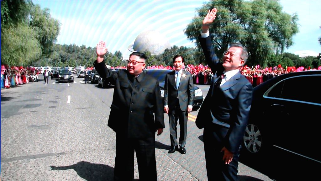 North Korean leader Kim Jong-un (L) and South Korean President Moon Jae-in wave to the crowd during a brief stop of their car parade through Pyongyang on Sept. 18, 2018, in this image from ...