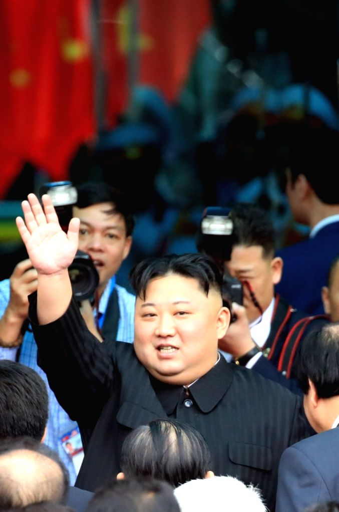 North Korean leader Kim Jong-un waves to a group of officials, citizens and journalists before boarding a train at the station in the Vietnamese border town of Dong Dang to head back to his ...